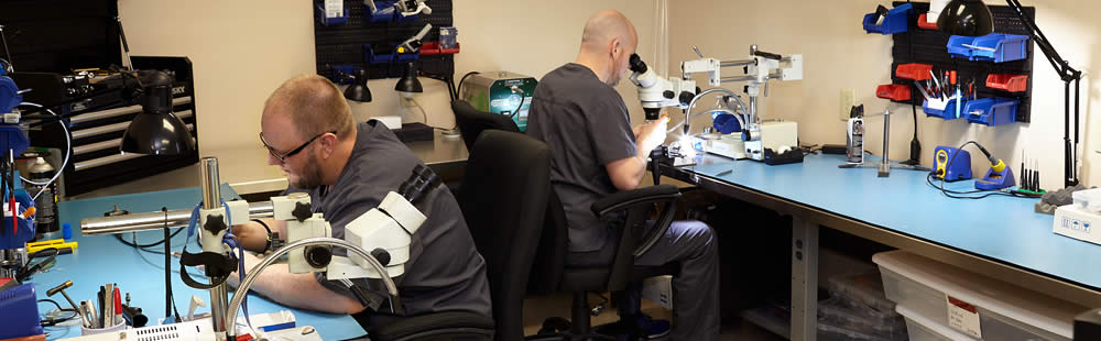 Surgical equipment repair by The Surgical Equipment People. Photo is of two repair technicians working on endoscopes in TSEP's Knoxville, TN repair facility.